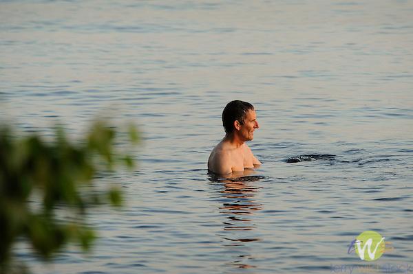 Adult man in lake watching sunset.