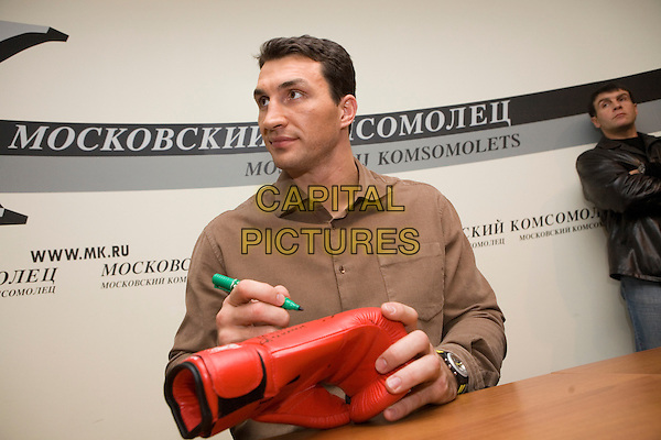 Wladimir Klitschko.Press conference in the newspaper the Moscow member of the Komsomol, Russia..November 23rd, 2006.half length signing autographs brown shirt .CAP/PER/AM.©AM/PersonaStars/CapitalPictures
