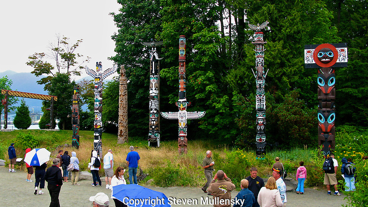 Visitors enjoy a visit to the Totem Pole Park in Stanley Park in the city of Vancouver, BC, Canada.