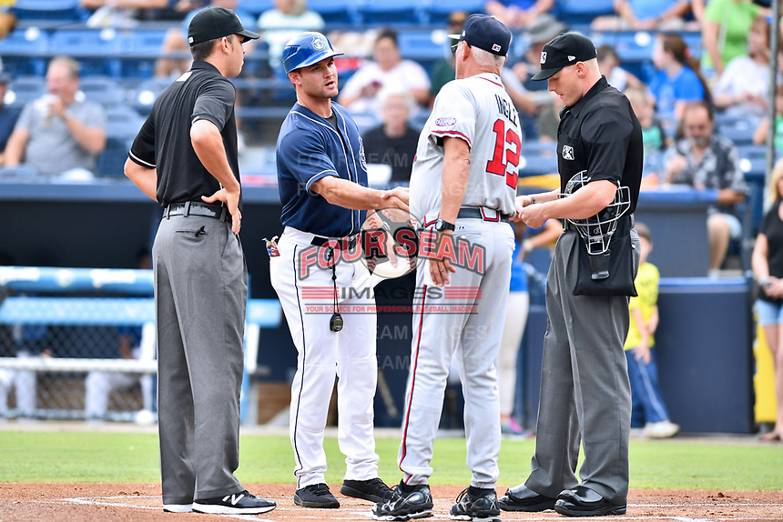 First base umpire Emil Jimenez, Asheville Tourists manager Warren Schaeffer (13), Rome Braves manager Randy Ingle (12) and home plate umpire Mike Snover before a game between the Rome Braves and the Asheville Tourists at McCormick Field on July 27, 2017 in Asheville, North Carolina. The Braves defeated the Tourists 6-3. (Tony Farlow/Four Seam Images)