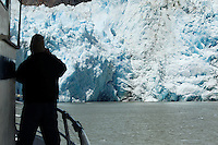 Tourist on boat at terminus face of Sawyer Glacier, Tracy Arm, Southeast Alaska, USA