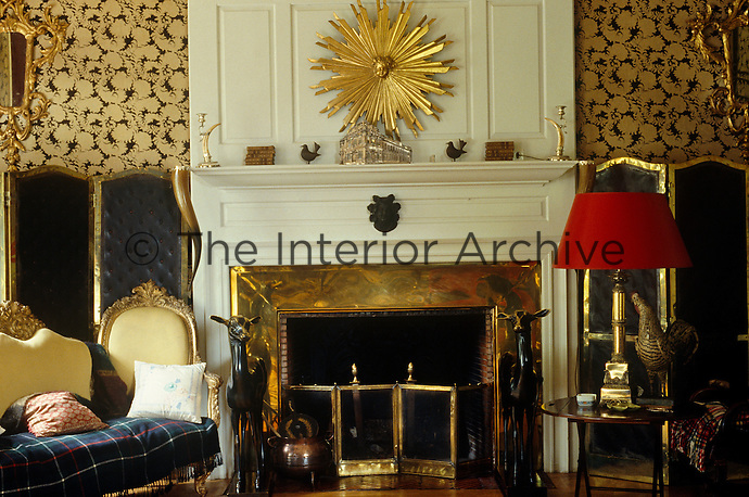 A gilt sunburst hangs above the fireplace in this eclectic sitting room
