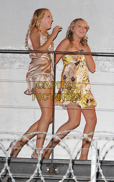 AMANDA & SAM MARCHANT .At the Grand Final of Big Brother 8.Elstree Studios, Borehamwood, Hertfordshire, England,.31st August 2007 .Herts full length twins runners up gold yellow and white print mini dress dresses.Ref: CAP/ROS.©Steve Ross/Capital Pictures