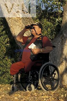 Disabled male in wheelchair, birding, using binoculars