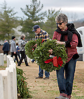STAFF PHOTO JASON IVESTER --12/13/2014--<br /> Latrice Sherman and her husband Fred Sherman, both of Fayetteville place wreaths at headstones on Saturday, Dec. 13, 2014, following the Wreaths Across America ceremony at the Fayetteville National Cemetery. Wreaths were placed at each of the 7100 veteran graves in the cemetery.