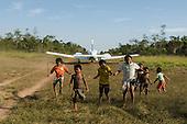 Mato Grosso State, Brazil. Aldeia Metuktire (Kayapo). Funai plane leaving  the airstrip, boys enjoying the wake from the engines.