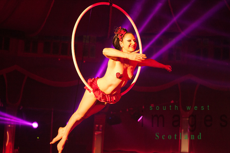 Big Burns Supper 2014, Dumfries, Le Haggis, almost naked female acrobat hanging finely balance from a hoop suspended from the ceiling in the Spiegeltent.