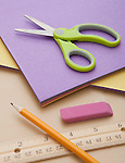 Studio shot of colored paper, scissors and pencil