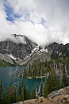 Dragontail Peak (left) and Colchuck Peak sit shrouded in cloud-cover above Alpine Lake in the Cascade Mountains in Washington.