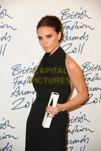Victoria Beckham.British Fashion Awards 2011 at Savoy Hotel, Srand, London, England..28th November 2011.half length black dress sleeveless halterneck award trophy .CAP/CAS.©Bob Cass/Capital Pictures.