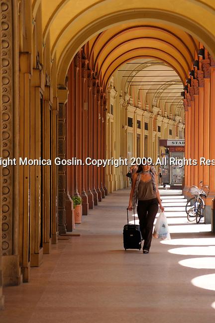 A woman walks down a sidewalk in Bologna, Italy.