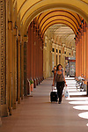 A woman walks down a sidewalk in Bologna, Italy.