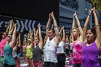 "Thousands of yoga practitioners pack Times Square in New York to participate in a mid-day Bikram Yoga class on the first day of summer, Friday, June 21, 2013. The 11th annual Solstice in Times Square, ""Mind Over Madness"",  stretches the yogis' ability to block out the noise and the visual clutter that surround them in the Crossroads of the World"". (© Frances M. Roberts)"