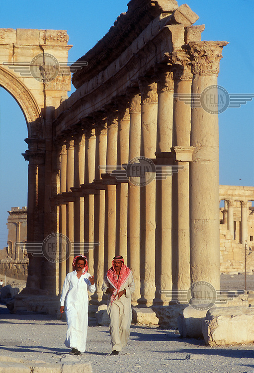 Two men walk through the ancient ruins of Palmyra (or Tadmor in Arabic). The site dates back to the Neolithic period and was first mentioned in the second millennium BC as a caravan stop. It later came under the Seleucid Empire and then under the Roman Empire.<br /> In May 2015 Islamic State (IS) forces fighting the Syrian government of President Assad took control of the modern settlement of Tadmur and the historic site. There are fears that the priceless treasures could fall victim to IS's iconoclastic destruction that has seen museums and ancient sites across Syria and Iraq destroyed.