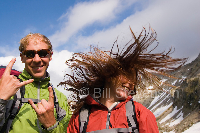 A picture of a woman tossing her hair as her boyfriend looks on while hiking near Chamonix France