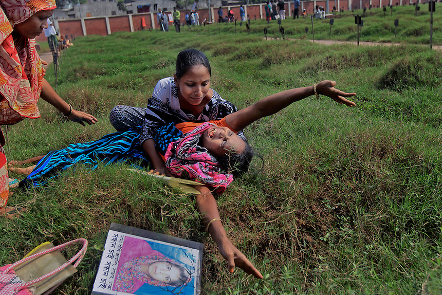 Nazma Begum, the mother of Aakhi, a victim of the April 24 Rana Plaza building collapse, cries at her daughter's graveyard after government laboratory tests identified 157 persons out of the 322 unidentified victims in Dhaka, Bangladesh, Thursday, Nov. 7, 2013.