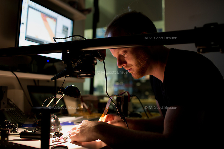 Postdoc Gordon Wetzstein works on a camera sensor in his office in the Camera Culture group in MIT's Media Lab in Cambridge, Massachusetts, USA.  Wetzstein's work in computational photography focuses on changing the way sensors and displays capture and project light. Here, Wetzstein is working on a printed filter that would alter the way the sensor captures light and which would then be decoded computationally to display captured images in novel ways. The work might be applied to create things such as glasses-free 3D viewing or ultra-high-definition imagery, among other possible uses.