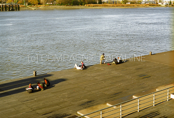 People relaxing on the Jordaenskaai on the borders of the Schelde river in Antwerp (Belgium, 08/11/2005)