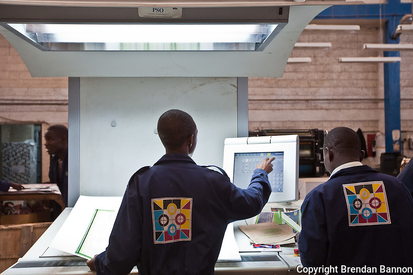 Print technicians monitoring the color balance on brochures for Safaricom, a Kenyan mobile phone company.