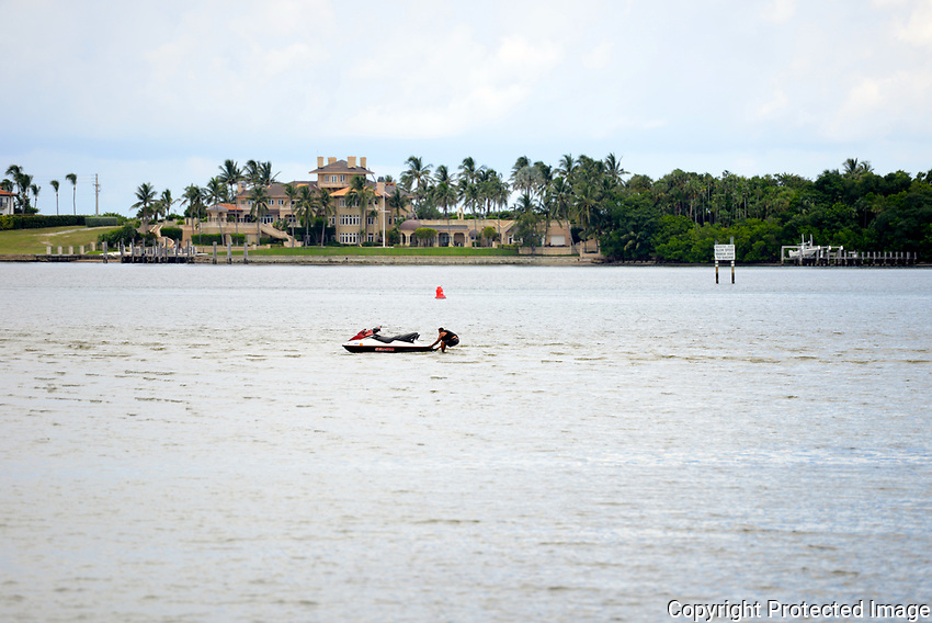 """Jet Ski """"grounded"""" on sand bar with owner attempting to free it. About an hour later the tide started to come in and floated the jet ski."""