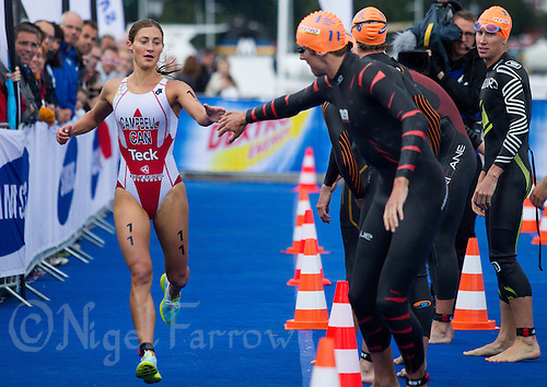 26 AUG 2012 - STOCKHOLM, SWE - Lauren Campbell (CAN) of Canada (left) tags team mate Andrew Yorke (CAN) (second from left) during the 2012 ITU Mixed Relay Triathlon World Championships in Gamla Stan, Stockholm, Sweden .(PHOTO (C) 2012 NIGEL FARROW)
