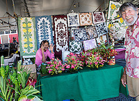 An aunty holding her cell phone waves and a local senior resident smiles at the viewer at the Hilo Farmers Market on the Big Island of Hawai'i.