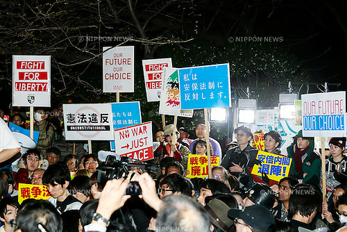 People hold anti-war placards during a protest against new security legislation which comes into effect form today March 29, 2016, in Tokyo, Japan. Last Tuesday, Prime Minister Shinzo Abe's Cabinet decided to give the green light to a change in the interpretation of the country's post war constitution that will allow Japan's Self-Defence Forces to fight alongside the US and other allies in overseas conflicts. The new legislation could also see Japanese Self-Defence Forces dispatched to United Nations peacekeeping operations. Many Japanese oppose the new legislation and fear that it could see their country being dragged into overseas conflicts. The Abe government in turn sees the change as a chance to become more actively involved in the international community. (Photo by Rodrigo Reyes Marin/AFLO)