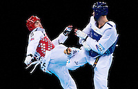 04 DEC 2011 - LONDON, GBR - Aaron Cook (GBR) (on left, in red) battles with Nicolas Garcia (ESP) (on right, in blue) during their men's -80kg category semi final contest at the London International Taekwondo Invitational and 2012 Olympic Games test event at the ExCel Exhibition Centre in London, Great Britain .(PHOTO (C) NIGEL FARROW)