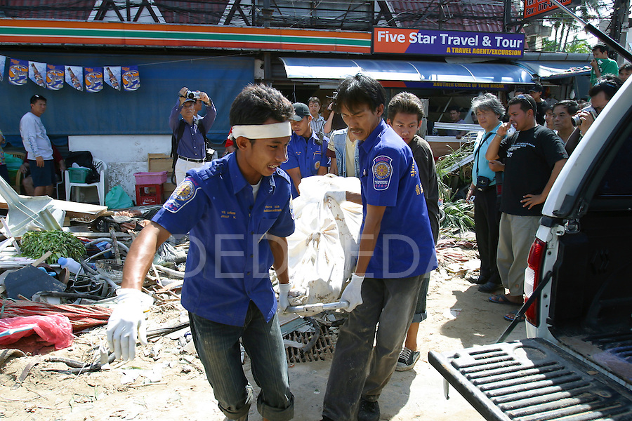 Emergency crews remove a body from a building after a series of tsunamis hit Patong Beach on Phuket Island, Thailand. On December 26, 2004, a major earthquake generated tsunamis that ravaged coastlines from Southeast Asia to Africa. Approximately 275,000 people were killed and tens of thousands were left homeless, making it one of the deadliest natural disasters in modern history.