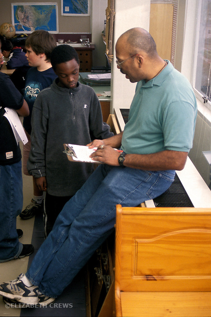 Berkeley, CA African American male teacher reviewing student's work with him in fifth grade classroom