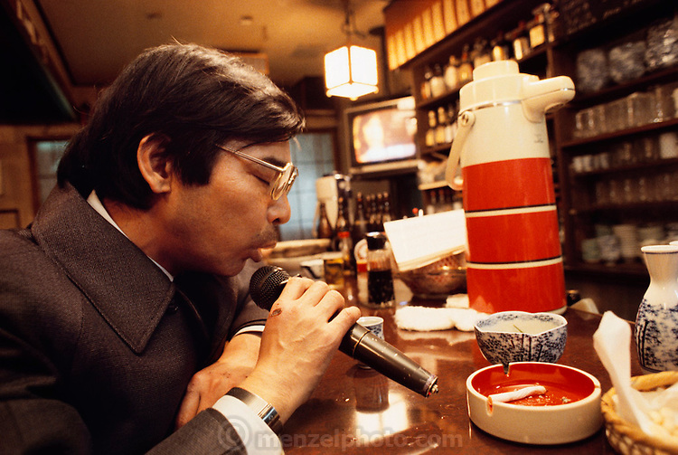 Several times a week, Kazuo Ukita relaxes after work by stopping at a karaoke bar for a cigarette, a glass of sake, and a crack at the microphone. Japan. Published in Material World: A Global Family Portrait page 51. The Ukita family lives in a 1421 square foot wooden frame house in a suburb northwest of Tokyo called Kodaira City.