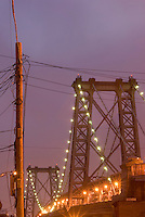 The Williamsburg Bridge,  seen from the Williamsburg neighborhood of Brooklyn, Illuminated at Dusk, Telephone Poles in foreground....Brooklyn, New York City, New York State, USA