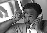 African-American Doctor on phone with hand to forehead, holding glasses, x-rays in background; reflective; concentrating; consulting; advising. occupations, medical, Black man, telephone, communication, black and white image. Dave Johnson.