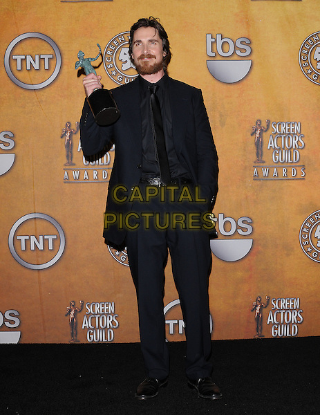 CHRISTIAN BALE.The 17th Annual Screen Actors Guild Awards held at The Shrine Auditorium in Los Angeles, California, USA..January 30th, 2011.pressroom press room full length black suit winner trophy award beard facial hair hand in pocket                                                                 .CAP/RKE/DVS.©DVS/RockinExposures/Capital Pictures.