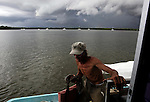 Scot Janikula, 50, who lives on his boat in Estero Bay, climbs aboard after getting gasoline in town, arriving just before a summer storm. Most who live on their boats have a plan for where to go during a tropical storm or hurricane, and many of the boats will withstand up to a category four storm.