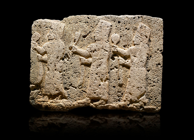 Hittite monumental relief sculpted orthostat stone panel of a Procession Limestone, Karkamıs, (Kargamıs), Carchemish (Karkemish), 900-700 B.C. Anatolian Civilisations Museum, Ankara, Turkey.<br /> <br /> It is a depiction of three marching female figures in long dress with a high headdress at their head. These women are considered to be the nuns of the Goddess Kubaba. The figures in the front and behind have a round mirror in their right hand while the figure in the middle has a bunch of spica in her right hand. Figures carry objects similar to a sceptre in their left hand.  <br /> <br /> Against a black background.