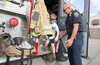 NWA Democrat-Gazette/DAVID GOTTSCHALK Tully Eldridge, a kindergarten student at Holcomb Elementary School, is assisted out of Ladder 7 by Captain Kyle Flynn, with the city of Fayetteville Fire Department, after touring the inside at the school in Fayetteville. Kindergarten through second grade students had the opportunity to learn how to leave a room safely in case of a fire, learn fire safety tips and tour Ladder 7 with members of the Fire Department.