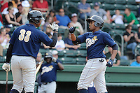 Outfielder Yeicok Calderon (25) of the Charleston RiverDogs, right, is congratulated by Reymond Nunez (33) after scoring a run in a game against the Greenville Drive on Sunday, May 19, 2013, at Fluor Field at the West End in Greenville, South Carolina. Charleston won, 9-7. (Tom Priddy/Four Seam Images)