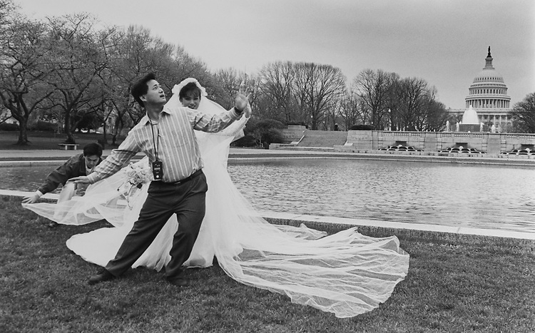Wedding/portrait photographer, Linh Trinh of California, Light meter hanging around his neck, shows Mylac Tvan, bride-to-be, how to pose for her portrait on April 4, 1994. (Photo by Laura Patterson/CQ Roll Call via Getty Images)