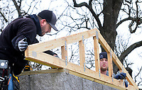 NWA Democrat-Gazette/DAVID GOTTSCHALK Tony Guppy (left), of Guppy Construction of Bentonville, is assisted Monday, March 12, 2018, by Kainen Lee as he positions a roof truss on a new bathroom facility at the Little Flock City Park. The park, that was established in 1970,  is under going renovations and improvements that include the bathroom facility and work on the gazebos.
