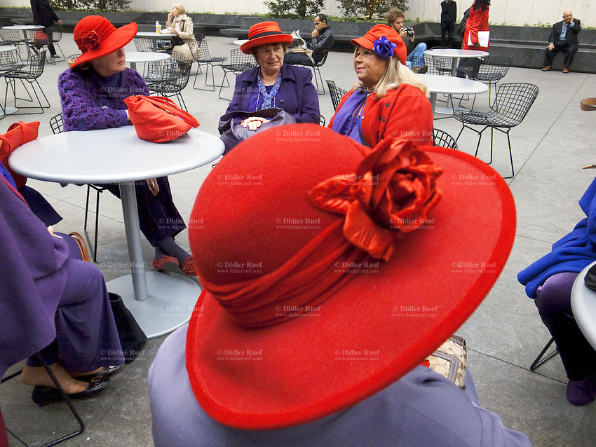 USA. New York City. A group of elderly women, all wearing a red hat and a purple jacket, seat on a square in Midtown Manhattan ( 43rd Street / 6Avenue). 26.10.2011 © 2011 Didier Ruef