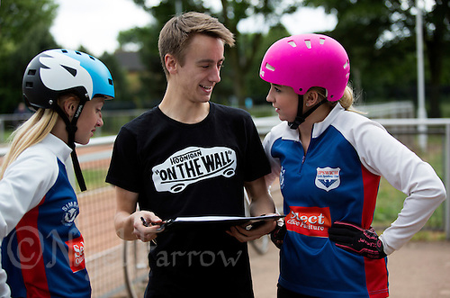 21 JUN 2015 - LONDON, GBR - Charlie-Jane Herbert (right) of Ipswich Eagles, watched by team mate Chloe Pearce (left), talks in the pits with team manager Richard Fellgett (centre) during their South East League Two cycle speedway fixture against East London at Canning Town Recreation Ground in London, Great Britain (PHOTO COPYRIGHT © 2015 NIGEL FARROW, ALL RIGHTS RESERVED)