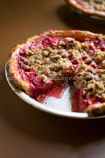 Closeup of a strawberry rhubarb pie topped with crumb topping. In a pie pan with one slice removed.
