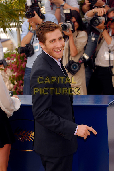 "JAKE GYLLENHAAL.Photocall for ""Zodiac"" during the 60th International Cannes Film Festival, Cannes, France..May 17th, 2007.half length stubble facial hair black suit jacket looking over shoulder.CAP/KRA.© Persun/Capital Pictures"