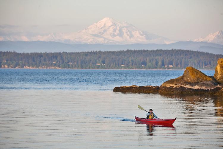 San Juan Islands, Sea kayaker, woman, Mount Baker, Clark Island Marine State Park, Salish Sea, Washington State, Pacific Northwest, U.S.A., model released,