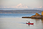 San Juan Islands, Sea kayaker, woman, Mount Baker, Clark Island Marine State Park, Salish Sea, Washington State, Pacific Northwest, U.S.A., model released,