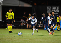 LAKE BUENA VISTA, FL - JULY 26: Yordy Reyna of Vancouver Whitecaps FC dribbles away from Gadi Kinda of Sporting KC and Ilie Sánchez of Sporting KC during a game between Vancouver Whitecaps and Sporting Kansas City at ESPN Wide World of Sports on July 26, 2020 in Lake Buena Vista, Florida.