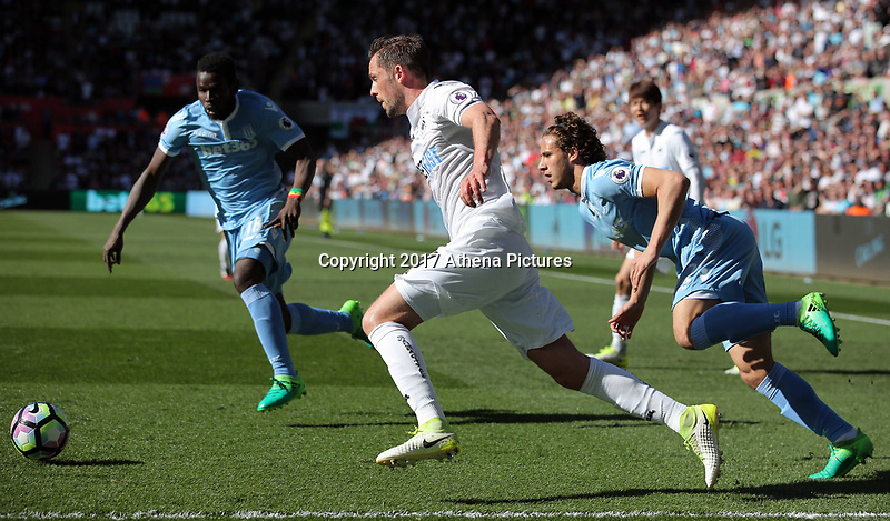 SWANSEA, WALES - APRIL 22: Ramadan Sobhi of Stoke City (R)  challenges Gylfi Sigurdsson of Swansea City (C) during the Premier League match between Swansea City and Stoke City at The Liberty Stadium on April 22, 2017 in Swansea, Wales. (Photo by Athena Pictures/Getty Images)