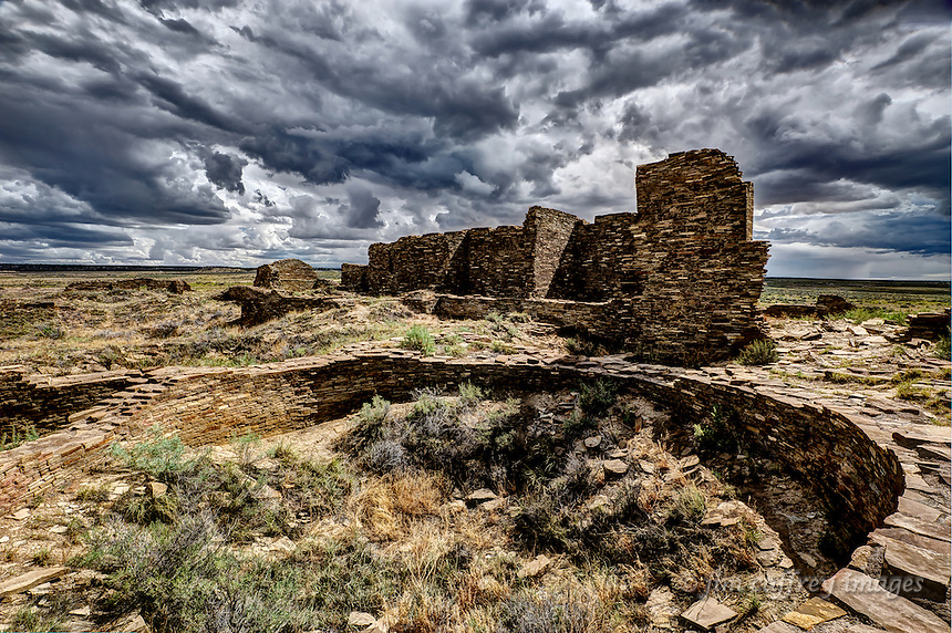 The ruins of a large kiva and pueblo walls at Pueblo Pintado, an outlier of Chaco Canyon, under stormy skies.