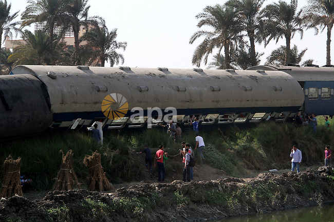 Egyptians check the wreckage of a train after it derailed near the village of Al-Ayyat in Giza on the southern outskirts of the capital Cairo, on September 7, 2016. The conductor suddenly hit the breaks when he spotted a problem with the tracks, causing three carriages to overturn, officials said. Photo by Stranger